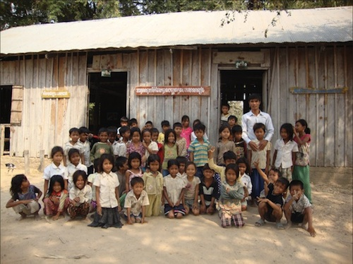 Koh Broteal Elementary school students and their teacher stand in front of the current building.
